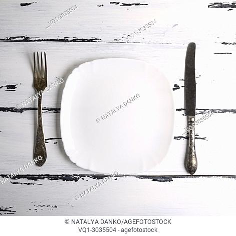 empty white ceramic plate with a fork and knife on a white wooden background, top view