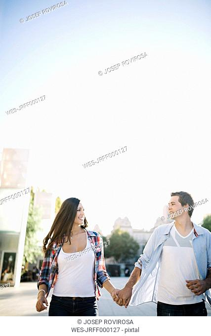 Spain, Reus, young couple in love walking around in the city