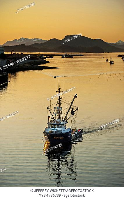 Commercial fishing vessel sailing through channel in Sitka, Alaska, USA