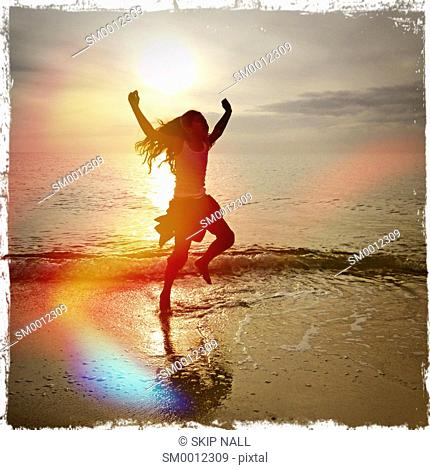 Little girl dancing on the ocean shoreline