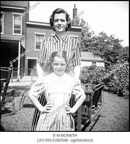 Mother and daughter in striped dresses smile at camera circa 1950