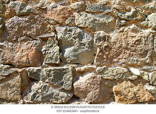 Natural background of the brown colored stone wall
