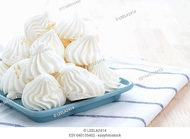 Candy meringue pieces placed in a blue plate with a cup of tea. White with blue cloth pad under plates. All on a wooden table
