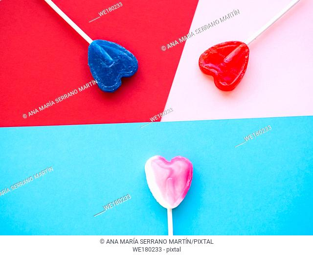 Several lollipops on a red, pink and blue background