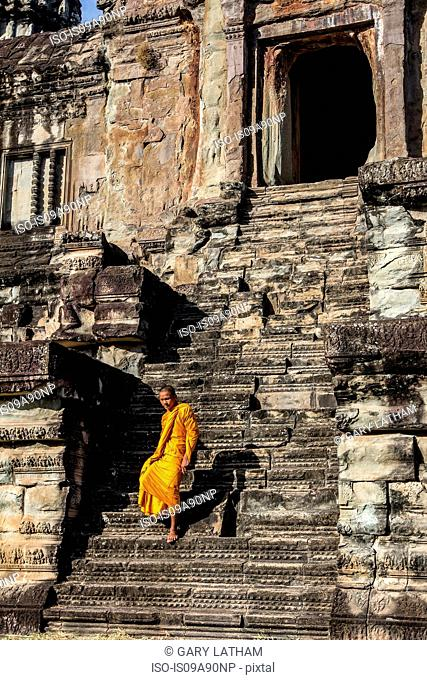 Young Buddhist monk walking down steps at temple in Angkor Wat, Siem Reap, Cambodia