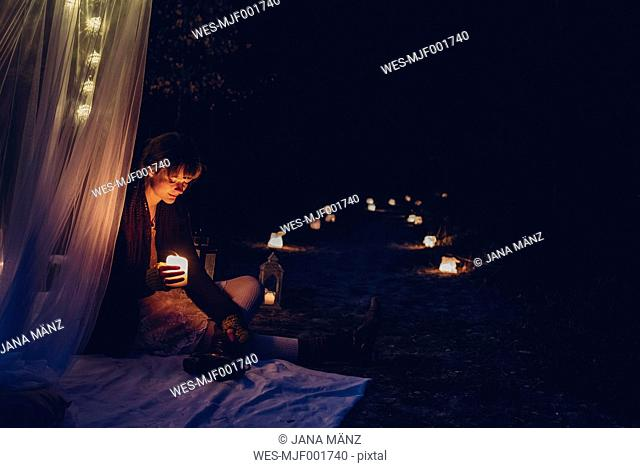 Woman in a romantic camp lighted by candle light in nature