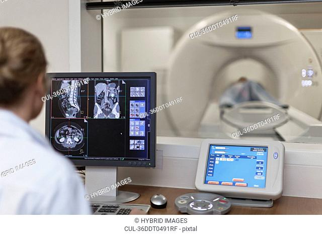Doctor operating CT scanner in hospital