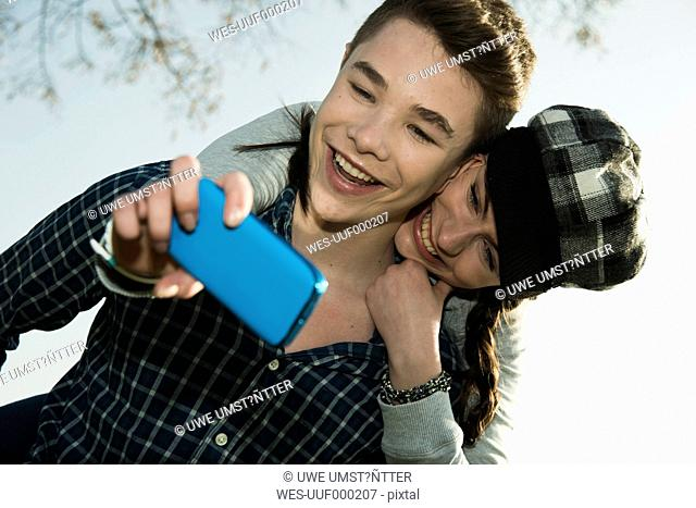 Portrait of teenage couple photographing themselves with smartphone