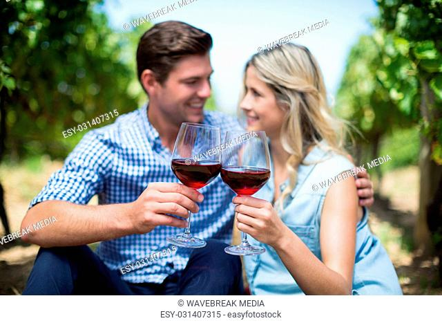 Couple with wineglasses embracing at vineyard