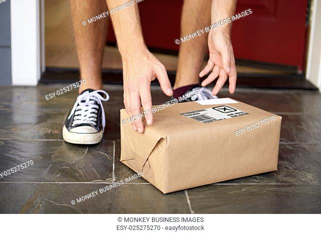Close Up Of Man Collecting Parcel Delivery Outside Door