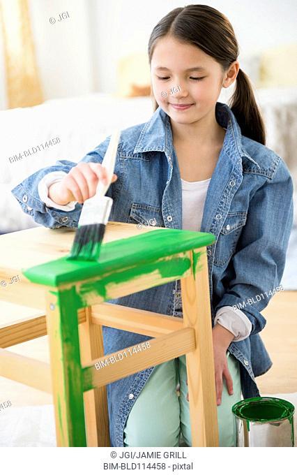 Mixed race girl painting stool