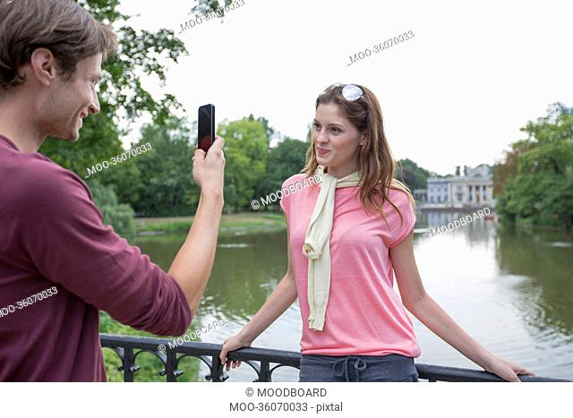 Young man photographing woman through cell phone at lakeside