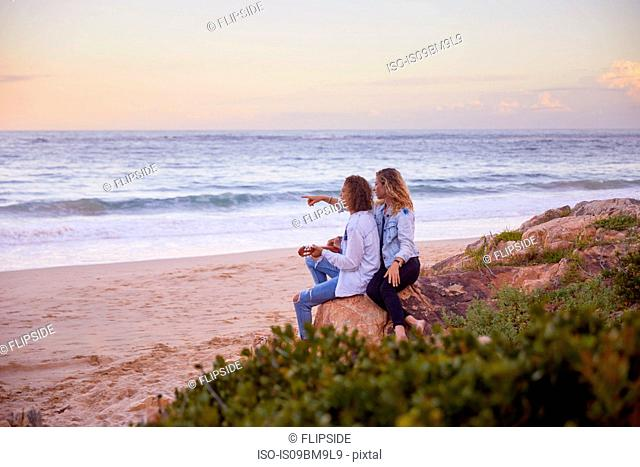 Couple relaxing on beach, Plettenberg Bay, Western Cape, South Africa