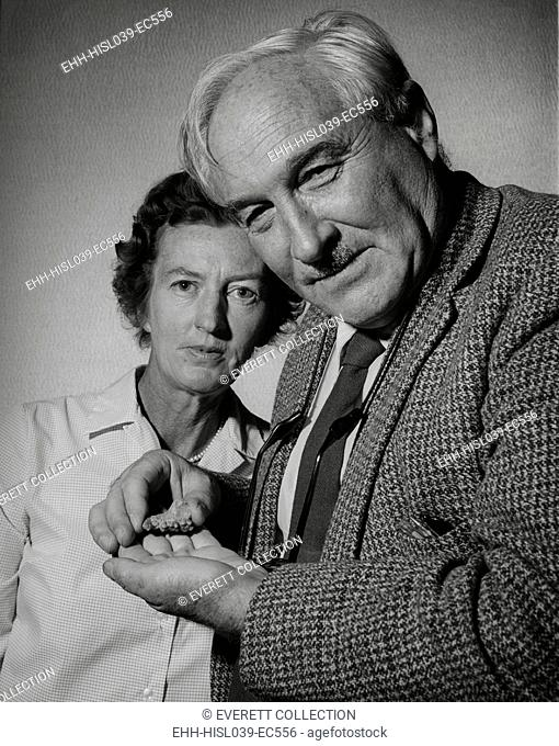 Anthropologists Mary Douglas Leakey and her husband Louis Leakey. Louis is holding the fragment of an early human jaw bone with molars. Ca. 1960s