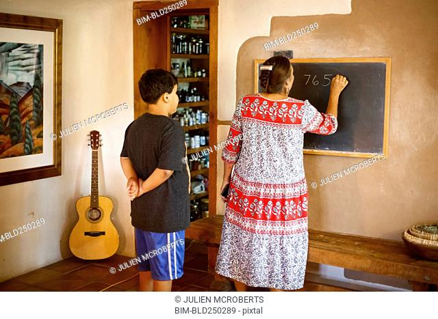 Woman writing equation on blackboard for son