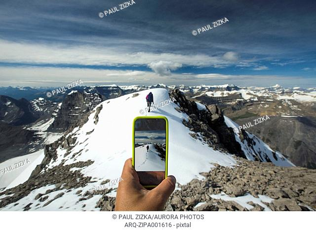 Person Taking Smartphone Picture Of Hiker Hiking On Cirrus Mountain In Alberta, Canada