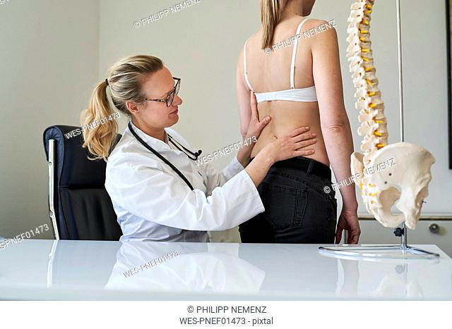 Female doctor examining back of patient in medical practice