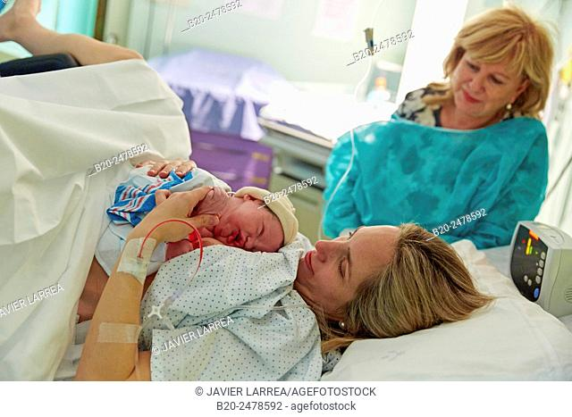 Mother holding newborn child in delivery room, Hospital Donostia, San Sebastian, Basque Country, Spain