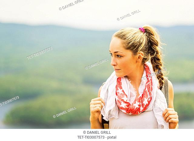 Portrait of young woman against green landscape