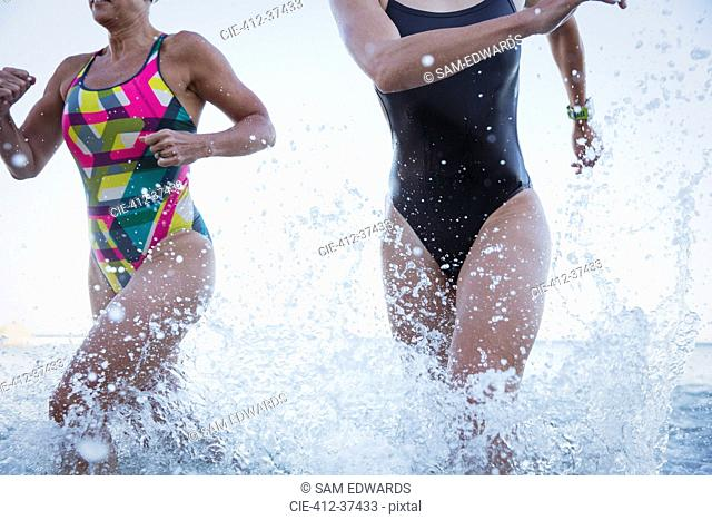 Female open water swimmers running and splashing in ocean surf