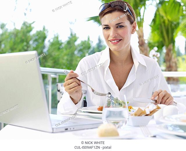 Portrait of young businesswoman having working lunch