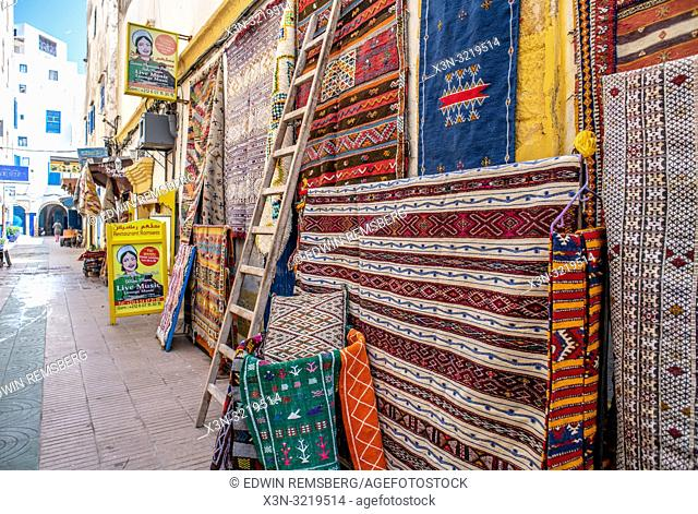 View Down a Street with Patterned Rugs in Foreground, Essaouira, Marrakesh-Safi, Morocco