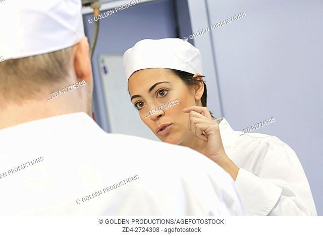 Restaurant kitchen workers talkingn