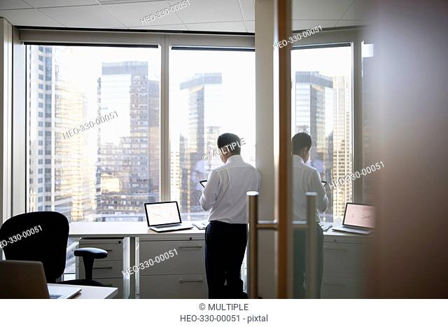 Businessman using digital tablet at highrise office window
