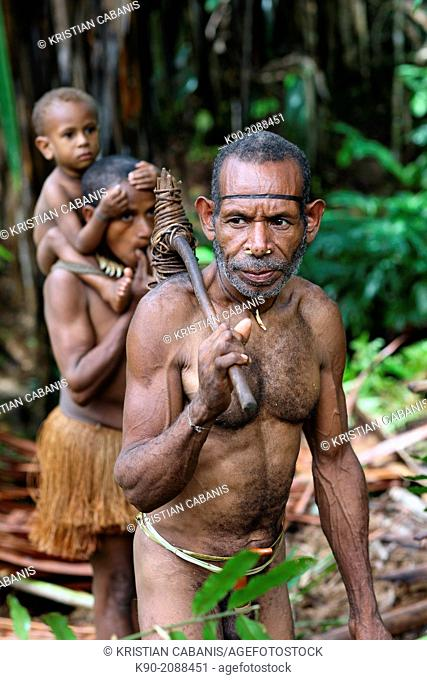 Kombai man standing in the jungle with stone axe his wife with kid in the background, Papua, Indonesia, Southeast Asia