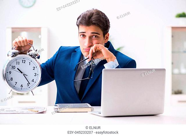 Businessman employee in urgency and deadline concept with alarm clock