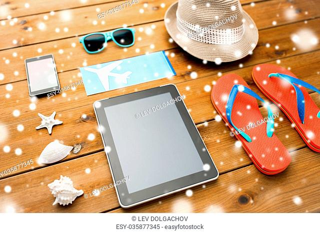 vacation, tourism, technology and objects concept - close up of tablet pc computer and travel stuff