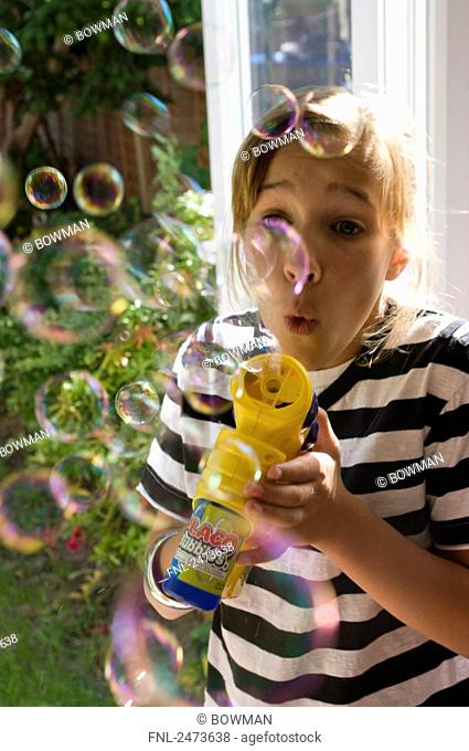 Close-up of girl blowing soap bubbles, England