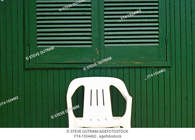 White Plastic Chair in front of Green Hut