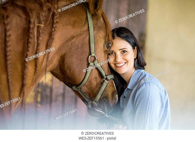 Portrait of smiling woman with a horse on a farm