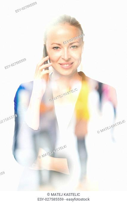 Beautiful young caucasian woman in business attire talking on smart phone on white background. Double exposure with abstract blur of business people overlay