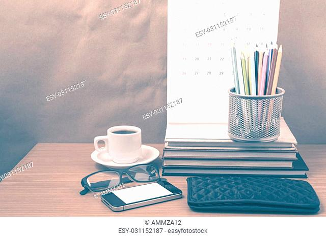 office desk : coffee with phone,wallet,calendar,color pencil box,stack of book,eyeglasses on wood background vintage style