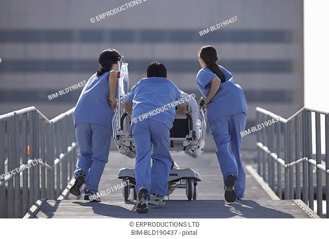 Asian medical professionals pushing gurney on roof