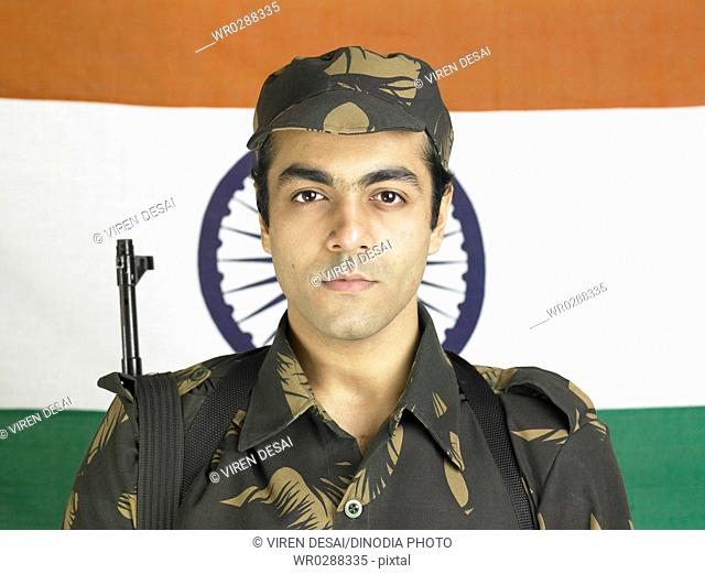 Indian army soldier with AK-47 gun in front of flag of India in background MR702A