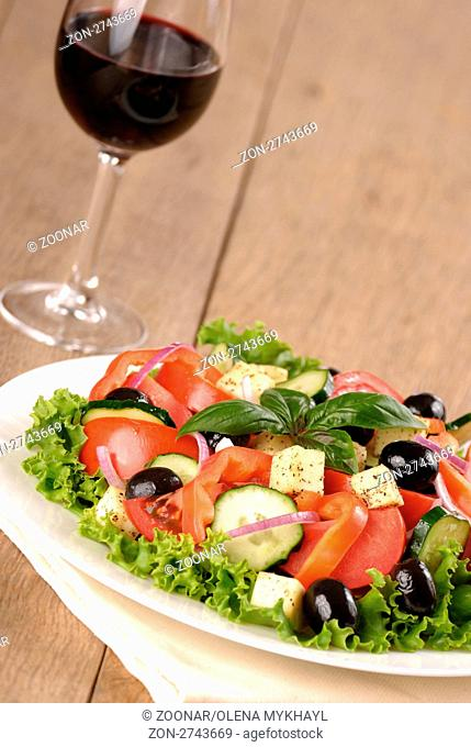 Greek salad and glass of red wine on the oak table