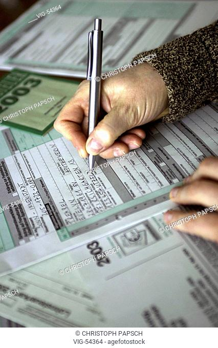 Completing of an income tax return. - BONN, GERMANY, 10/03/2004