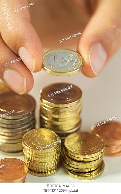 Man stacking Euro coins