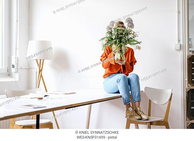 Young woman sitting on table holding flower vase in front of her face