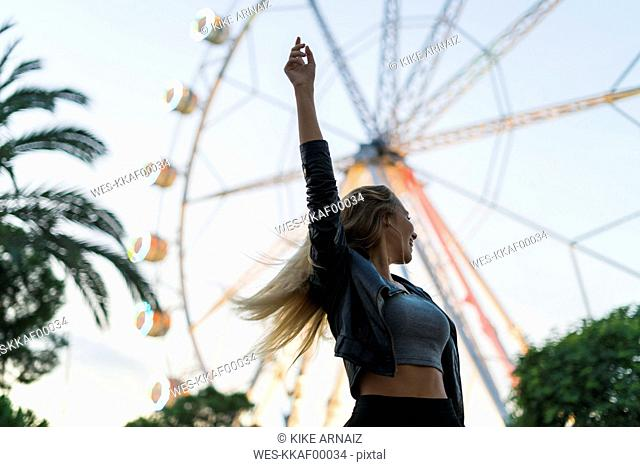 Enthusiastic young woman on a funfair with a ferris wheel