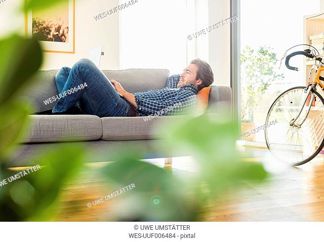 Young man lying on the couch using laptop