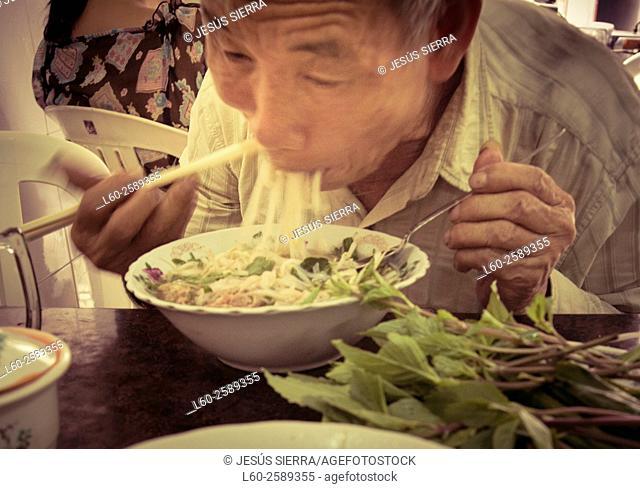 Old man eating Vietnamese food