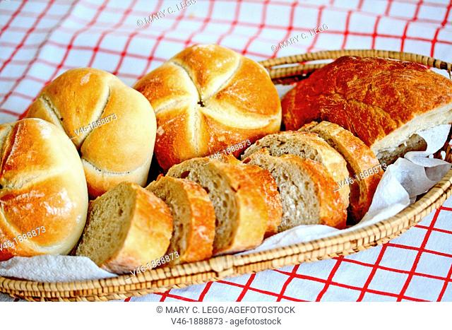 Bread basket on red striped tablecloth  Small open weave basket filled with bread rolls sliced soda bread and half-round rye