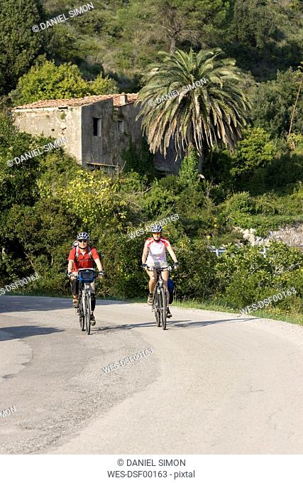 Italy, Tuscany, Capoliveri, Mountainbikers riding across country road