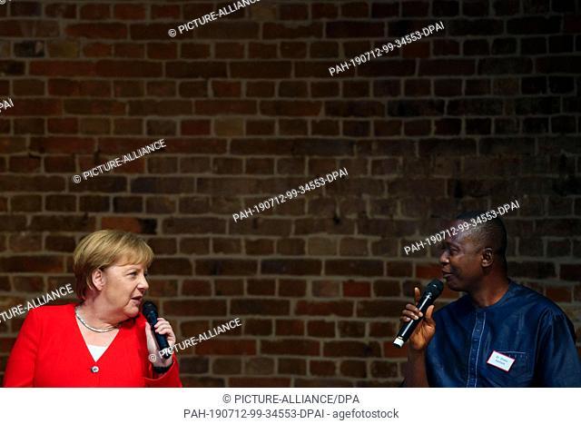 12 July 2019, Berlin: Federal Chancellor Angela Merkel (CDU, l-r) and Sheku Kamara, Director of the Conservation Society of Sierra Leone