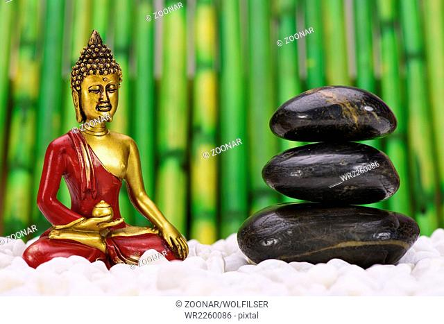 zen garden with buddha figure and stacked stones