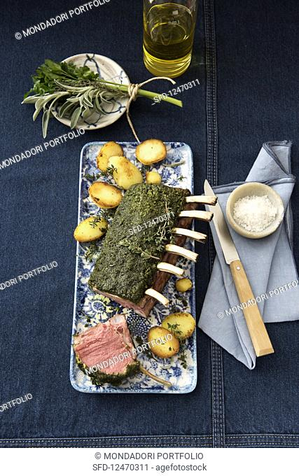 Lamb loin rack joint with a herb and mustard crust and potatoes